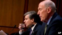 El director del FBI, Christopher Wray (centro) escucha al director nacional de Inteligencia, Dan Coats (derecha) durante su testimonio en la Comisión de Inteligencia del Senado en Washington, el martes, 13 de febrero de 2018.
