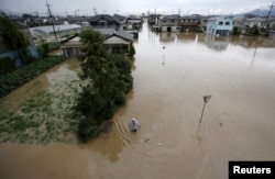 A man wades through a residential area flooded by the Kinugawa river, caused by typhoon Etau, in Joso, Ibaraki prefecture, Japan, September 10, 2015.