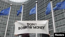 Students display a banner outside the EU Commission headquarters ahead of an European Union summit in Brussels December 8, 2011. European Union leaders will discuss proposals for tighter euro zone integration on December 8 to 9, with the aim of bringing d