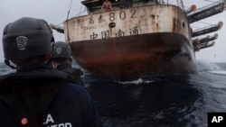 In this July 2021 photo provided by Sea Shepherd, crew members of the Ocean Warrior approach a Chinese-flagged vessel whose Indonesian crew said they had been stuck at sea for years.