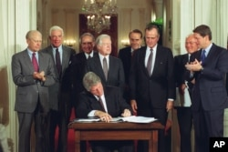 FILE - U.S. President Bill Clinton signs side deal of the three-nation North American Free Trade Agreement (NAFTA) at the White House, Washington, Sept. 14, 1993.
