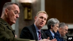 FILE - Acting Defense Secretary Patrick Shanahan, center, accompanied by Joint Chiefs Chairman Gen. Joseph Dunford, left, and Secretary of the Air Force Heather Wilson, speaks during a Senate Armed Services Committee hearing on Capitol Hill in Washington.