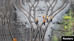 Workers inspect railway tracks for the Belt and Road freight rail route linking Chongqing, China, with Duisburg, Germany, at the Dazhou railway station in Sichuan province, China March 14, 2019.