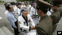"""FILE - Korean-American taekwondo grandmaster Jung Woo-jin, center, shakes hands with North Korean border soldiers as he offers a peace gesture of taekwondo """"dobok"""" robes on the North Korean side of the DMZ line outside Panmunjom, May 19, 2006."""