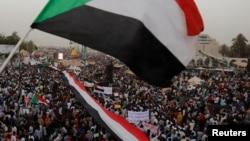 Ribuan pengunjuk rasa melambai-lambaikan bendera Sudan, seraya mengangkat poster dan meneriakkan slogan-slogan dalam sebuah unjuk rasa di depan Kementrian Pertahanan di Khartoum, Sudan 18 April 2019 (foto: Reuters/Umit Bektas)