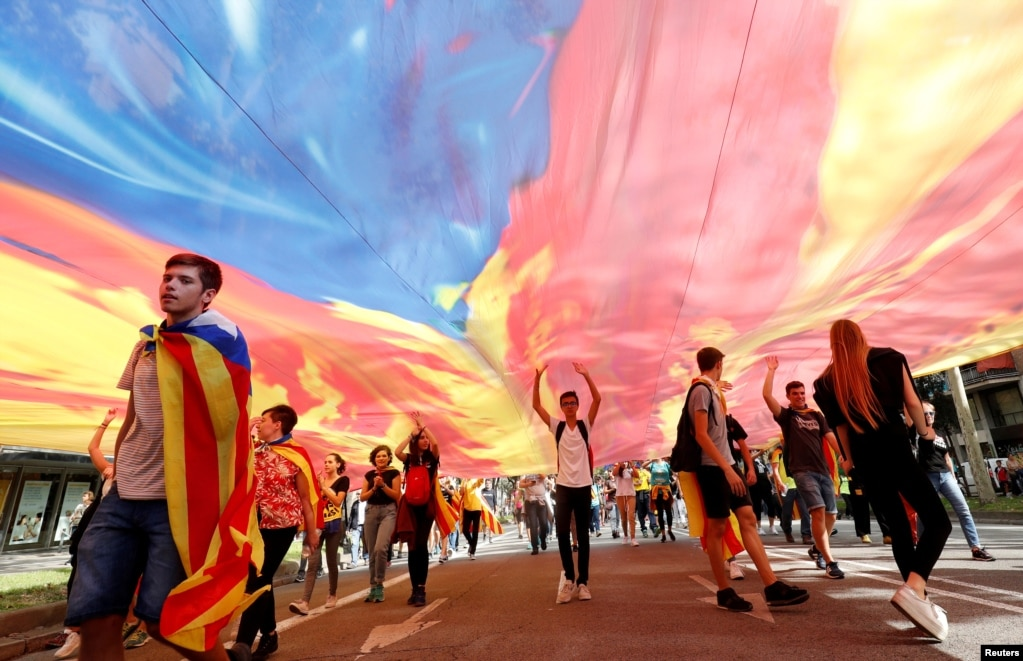 Demonstrators walk under an Estelada (Catalan separatist flag) as they march on Diagonal Avenue during Catalonia's general strike in Barcelona, Spain.