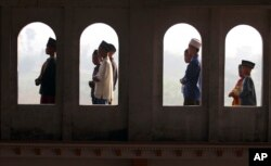 FILE - Muslim youths are seen through the windows of a mosque as they perform Eid al-Fitr morning prayers, Porong, East Java, Indonesia, August 8, 2013.