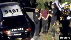 2018年2月14日在佛罗里达州帕克兰拍摄的一段视频中,警察在玛乔丽·斯通曼·道格拉斯高中校园附近逮捕克鲁兹给他戴上手铐。