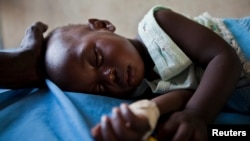 A young girl with malaria rests in the inpatient ward of the Malualkon Primary Health Care Center in Malualkon, in the South Sudanese state of Northern Bahr el Ghazal, June 1, 2012.