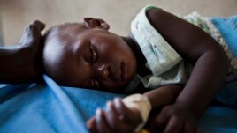 Young girl with malaria rests in a clinic in South Sudanese state of Nothern Bahr el Ghazal.