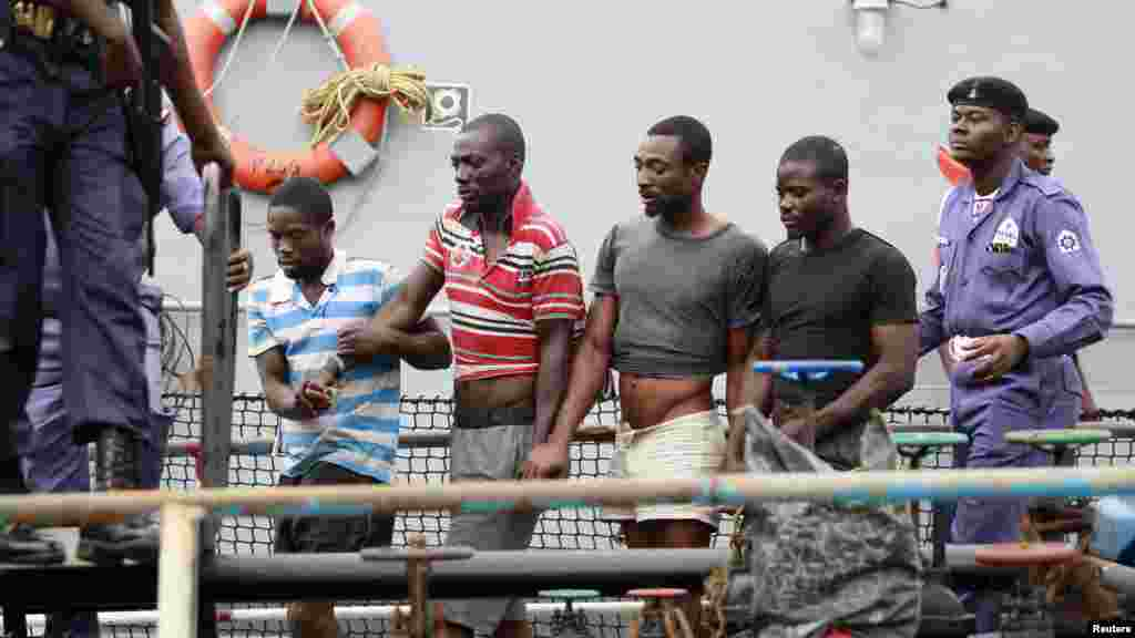 Suspected pirates are escorted aboard a naval ship after their arrest by the Nigerian Navy at a defence jetty in Lagos, August 20, 2013.