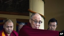Tibetan spiritual leader the Dalai Lama adjusts his robe upon arrival at a gathering to mark the anniversary of an unsuccessful revolt against China in 1959, in Dharmsala, India, Saturday, March 10, 2012. The head of Tibet's government in exile has blamed