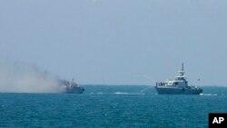 Egipatski ratni brod gasi požar na drugom brodu mornarice u Mediteranu, 16. jula 2015. Egipatski brod zapalio se nadomak obale Sinaja posle razmene vatre sa ekstremistima koji su pucali sa obale.