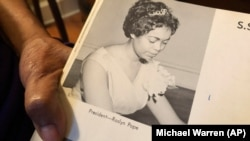 """In this March 4, 2020 photo, Roslyn Pope shows her Spelman College yearbook at her home in Atlanta. As a 21-year-old Spelman senior in March 1960, Pope wrote """"An Appeal for Human Rights."""" (AP Photo/Michael Warren)"""