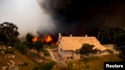 FILE - A fire rages near homes in San Marcos, California May 15, 2014.