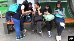 FILE - South Korean middle school students use their smartphones at a bus station in Seoul, South Korea, May 15, 2015.
