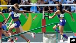 Les Américaines English Gardner et Allyson Felix, à droite, ratent le deuxième passage du témoin au 4x100 mètres dames lors des Jeux olympiques d'été de 2016 au stade olympique de Rio de Janeiro, au Brésil, 18 août 2016.