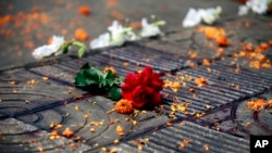 FILE - Flowers lie at the site where Avijit Roy was attacked and killed, in Dhaka, Bangladesh on Feb. 27, 2015. Roy, a prominent Bangladeshi-American blogger, known for speaking out against religious fundamentalism was hacked to death in the streets of Bangladesh's capital as he walked with his wife, police said Friday.