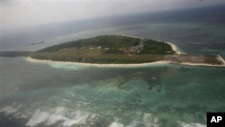 Photographed through the window of a closed aircraft, an aerial view shows Pagasa Island, part of the disputed Spratly group of islands, in the South China Sea located off the coast of western Philippines Wednesday July 20, 2011.