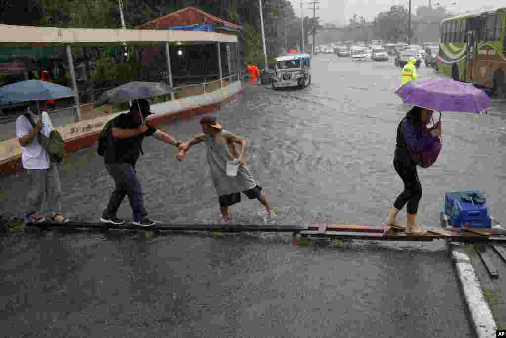 태풍 '네삿'이 필리핀을 강타한 가운데, 마닐라 시민들이 나무 구조물을 이용해 침수된 길을 건너고 있다.