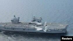 资料照片:在大西洋举行的一次演习期间,美国海军超级大黄蜂战机从英国海军伊丽莎白女王号航空母舰上方飞过。(2017年8月5日)