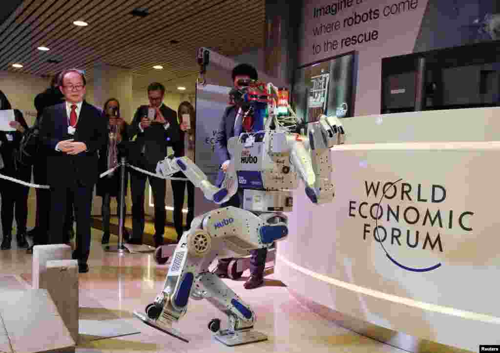 HUBO, a multifunctional walking humanoid robot performs a demonstration of its capacities next to its developer Oh Jun-Ho, Professor at the Korea Advanced Institute of Science and Technology (KAIST) during the annual meeting of the World Economic Forum (WEF) in Davos, Switzerland.