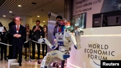 Technologies like robotics are seen as a driver of the so-called Fourth Industrial Revolution. HUBO, a walking humanoid robot performs a demonstration of its capacities next to its developer Oh Jun-Ho during the annual meeting of the World Economic Forum.