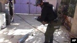 Приказ од аметерска снимка на која, како што се претпоставува, инспектор на ОН фотографира канистер во местото Моадамија, предградие на Дамаск.