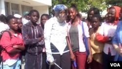 Juara anggar AS, Ibtihaj Muhammad (tengah), dalam sebuah kampanye pendidikan di Sekolah John F. Kennedy di Dakar, 2014. (VOA/Jennifer Lazuta)