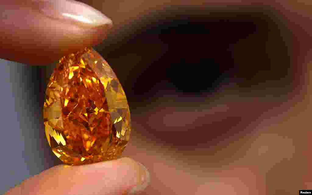 A member of Christie's staff displays The Orange, the world's biggest orange diamond, which weighs 14.82 carats during an auction preview in Geneva, Switzerland.