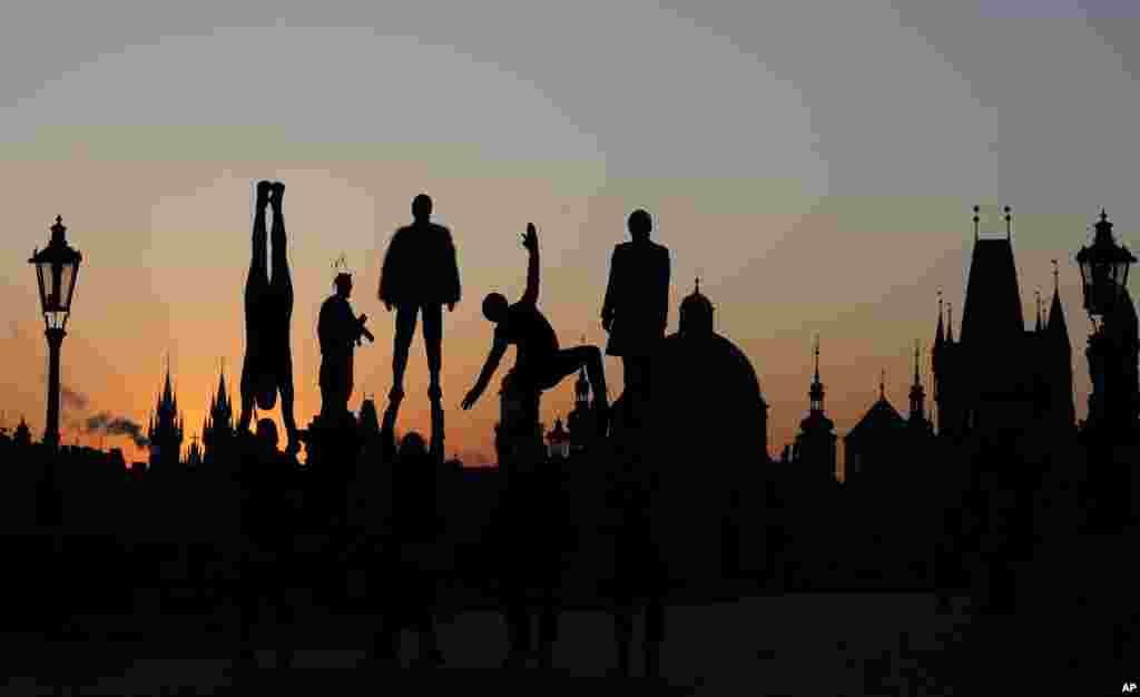 Street artists are silhouetted against the rising sun as they perform on the near empty Charles Bridge in Prague, Czech Republic.