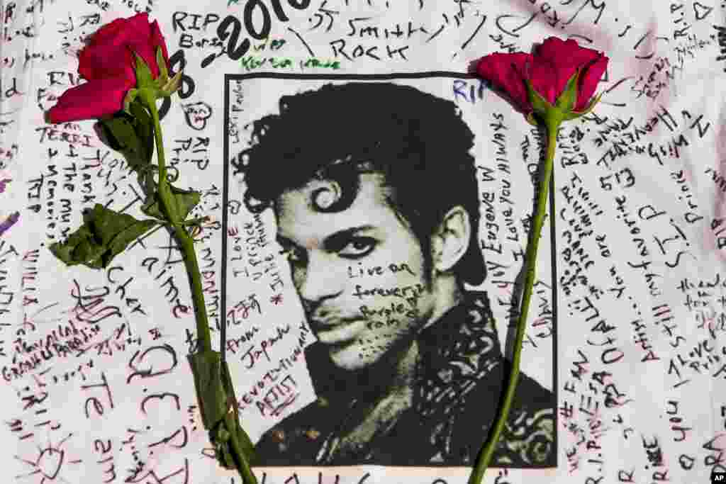 Flowers lay on a T-shirt signed by fans of singer Prince at a makeshift memorial place created outside Apollo Theatre in New York, April 22, 2016.