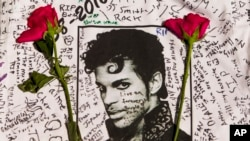FILE - Flowers lay on a T-shirt signed by fans of singer Prince at a makeshift memorial place created outside Apollo Theatre in New York, April 22, 2016.