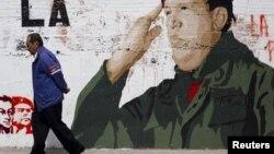 Un hombre pasa en Caracas junto a un mural con la figura de Chávez, cuya salud ha sufrido nuevas complicaciones en La Habana.