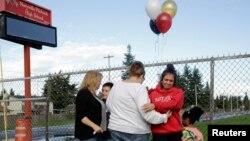 Una estudiante llora después de colocar flores y un globo en la cerca de la escuela secundaria Marysville-Pilchuck.