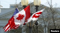A Canadian flag flutters between a U.S. flag and a Washington, D.C., flag in front of the White House in Washington, March 7, 2016. Preparations are under way for the official state visit of Canada's Prime Minister Justin Trudeau on Thursday.