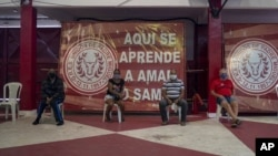 """In front of banners reading """"Here you learn to love samba,"""" residents suspected of suffering COVID-19 wait to be attended by Dr. Wille Baracho inside the Unidos de Padre Miguel samba school in the Vila Vintem slum of Rio de Janeiro, Brazil, May 24, 2020."""