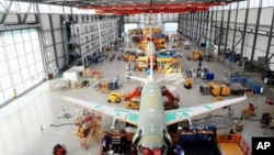 Airbus employess work on an A320 at the Airbus plant in Hamburg-Finkenwerder, northern Germany, February 23, 2011
