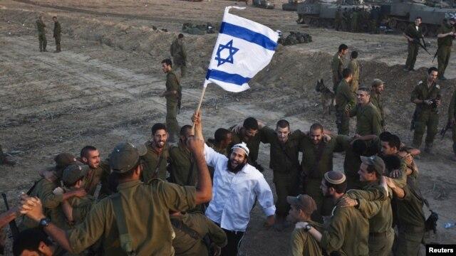 19일 가자 지구 접경 지역에서 국기를 휘날리는 이스라엘인과 군인들.