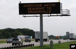 A sign warns of a Texas coastal hurricane watch as traffic passes by in Hutchins, Texas, Aug. 24, 2017.