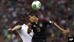 El mexicano Severo Meza (der.) y el estadounidense Herculez Gomez pelean por el balón en un partido clasificatorio de la Copa Mundial 2014.