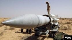 Un rebelde libio sobre un misil SA-5 SAM inutilizado por un ataque de la OTAN.