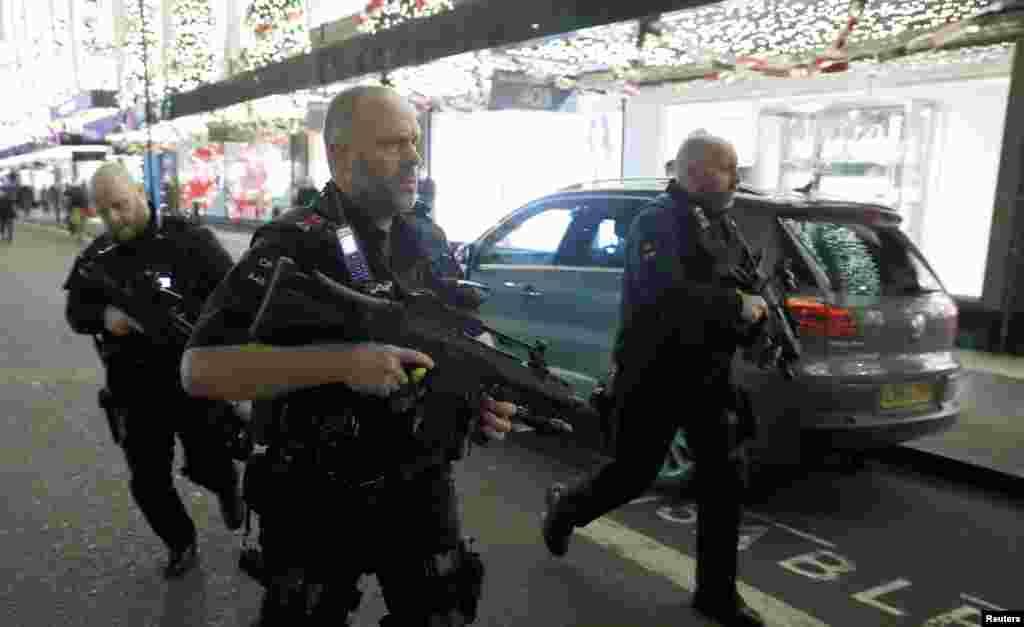 Oxford Caddesi'nde üç silahlı polis koşuyor.