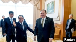 Secretary of State Mike Pompeo, right, and Kim Yong Chol, left, a North Korean senior ruling party official and former intelligence chief, arrive for a lunch at the Park Hwa Guest House in Pyongyang, North Korea