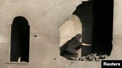 一名婦人檢視遭以色列砲彈襲擊後的房屋損毀情況