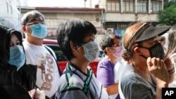 2020年1月30日,人們在菲律賓首都馬尼拉一商店前排隊購買口罩。(美聯社)
