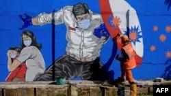 Seorang petugas tengah menggambar mural dengan pesan kampanye melawan virus Covid-19 di Jakarta, 27 Agustus 2020. (Foto: dok)