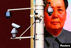 FILE - Security cameras in front of the giant portrait of former Chinese Chairman Mao Zedong on Beijing's Tiananmen Square, Nov. 11, 2012.