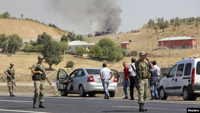 Turkish soldiers take security measures on a main road which connects eastern Turkish cities Bingol and Mus, as smoke rises from a burning vehicle attacked by PKK in the background, September 18, 2012.