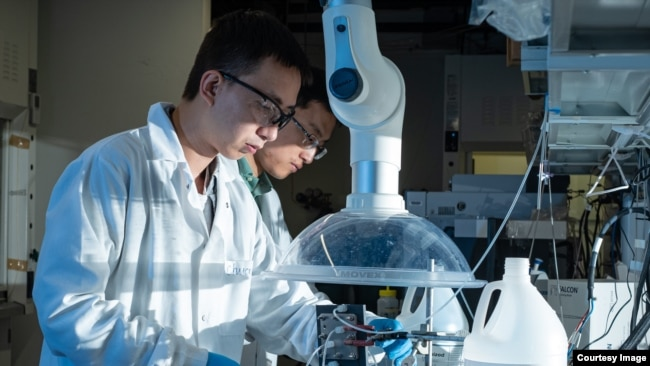 Rice postdoctoral researcher Chuan Xia, left, and chemical and biomolecular engineer Haotian Wang, adjust their electrocatalysis reactor to produce liquid formic acid from carbon dioxide. (Photo by Jeff Fitlow/Rice University's Brown School of Engineering